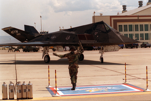 STAFF SGT. Gregory Auzenne, 8th Fighter Squadron crew chief, signals to Brig. GEN. Bruce Carlson during the pre-flight check before his final flight in the F-117A Nighthawk