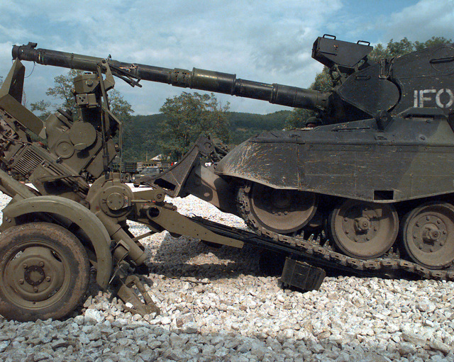 A Krauss-Maffei Leopard 1A5 Main Battle Tank Dozer, with IFOR markings, destroys a Serbian 20/3mm M55 A4 B1 Anti-aircraft Gun by driving over it at Danver Camp (DANBAT) in Doboj, Bosnia-Herzegovina, during Joint Endeavor. Operation Joint Endeavor is a peacekeeping effort by a multinational Implementation (IFOR), comprised of NATO and non-NATO military forces, deployed to Bosnia in support of the Dayton Peace Accords