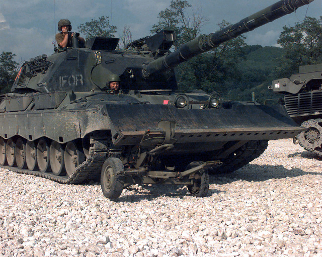 A Krauss-Maffei Leopard 1A5 Main Battle Tank Dozer, with IFOR markings, destroys a Serbian 20/3mm M55 A4 B1 Anti-aircraft Gun carriage by driving over it at Danver Camp (DANBAT) in Doboj, Bosnia-Herzegovina, during Joint Endeavor. Operation Joint Endeavor is a peacekeeping effort by a multinational Implementation (IFOR), comprised of NATO and non-NATO military forces, deployed to Bosnia in support of the Dayton Peace Accords