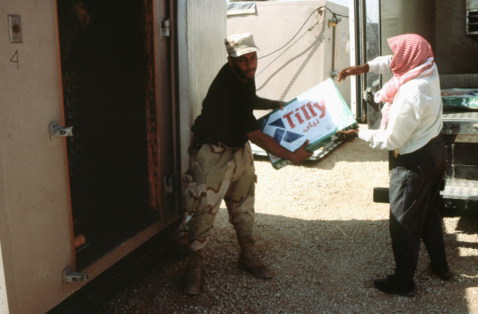 SENIOR AIRMAN Mike Correll, a Services SPECIALIST from the 99th Services Squadron, Nellis Air Force Base, Nevada restocks the refrigerated storage units with supplies at the Harvest Falcon dinning facility. A Saudi native assists in removing packages from the truck
