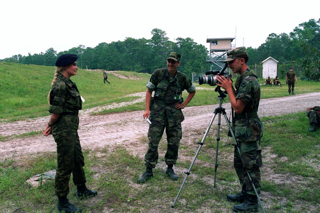 """A female Ukrainian Marine Medical Officer is interviewed by US Army Reserve Specialists (SPC) S.R. Cwalina, a Combat Photographer from 982nd Signal Company, attached to the 6th Marine Regiment during Operation COOPERATIVE OSPREY 96 held at Camp Lejeune, NC. Cooperative Osprey, under the Partnership for Peace program, will provide interoperability training in peacekeeping and humanitarian operations along NATO/IFOR standards, with an emphasis on individual and collective skills. The three NATO countries providing troops are the United States, Canada, and the Netherlands. The 16 """"Partnership for Peace"""" nations contributing troops are Albania, Austria, Bulgaria, Estonia, Georgia, Hungary, ..."""