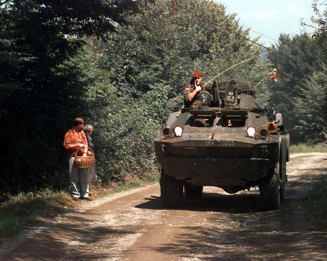 A Polish Army TABC-70 Armoured (Armored) Personnel Carrier (APC), with one crewmember standing up through the starboard hatch, is stopped on a dirt road beside two Bosnian civilians standing on the roadside. This Polish Army APC is part of the Nordic Polish Brigade (NPBDE), Multinational Division North (MND-N) Task Force Eagle, taking part in Operation Joint Endeavor, which is a peacekeeping effort by a multinational Implementation Force (IFOR), comprised of NATO and non-NATO military forces, deployed to Bosnia in support of the Dayton Peace Accords