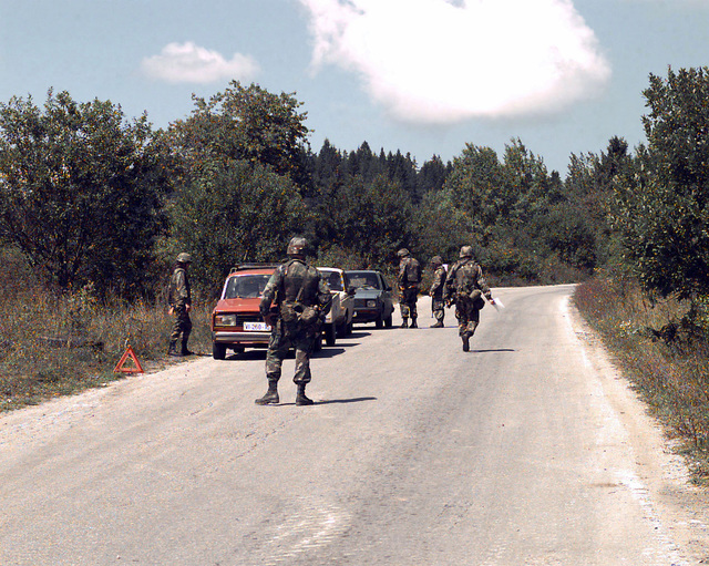 """Three civilian cars are stopped on a road and being searched by US Army soldiers at a checkpoint near """"Gator"""" Site, Bosnia-Herzegovina, during Operation Blast. Operation Blast is a smaller part of Operation Joint Endeavor, which is a peacekeeping effort by a multinational Implementation Force (IFOR), comprised of NATO and non-NATO military forces, deployed to Bosnia in support of the Dayton Peace Accords"""