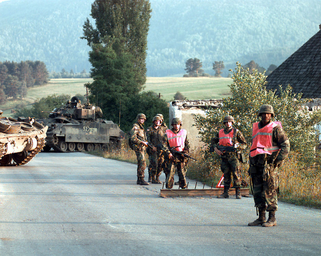 US Army soldiers and two M2A2 Bradley Infantry Fighting vehicles (IFV), one with IFOR markings, are on duty at a roadway checkpoint in Bosnia during Operation Joint Endeavor. Operation Joint Endeavor is a peacekeeping effort by a multinational Implementation Force (IFOR), comprised of NATO and non-NATO military forces, deployed to Bosnia in support of the Dayton Peace Accords