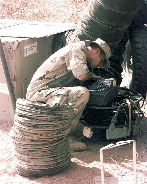 AIRMAN Jeremy S. Tichenor, a member of the 54th Combat Communications Squadron from Robbins Air Force Base Georgia troubleshoots a KY-68 Secure Field Telephone. These telephones will be used to provide secure and non-secure tactical communications to the leadership here, and will also provide an occasional morale call for the troops deployed here in support of Desert Focus, the relocation of Operation SOUTHERN WATCH (monitoring the no-fly zone over Iraq) personnel