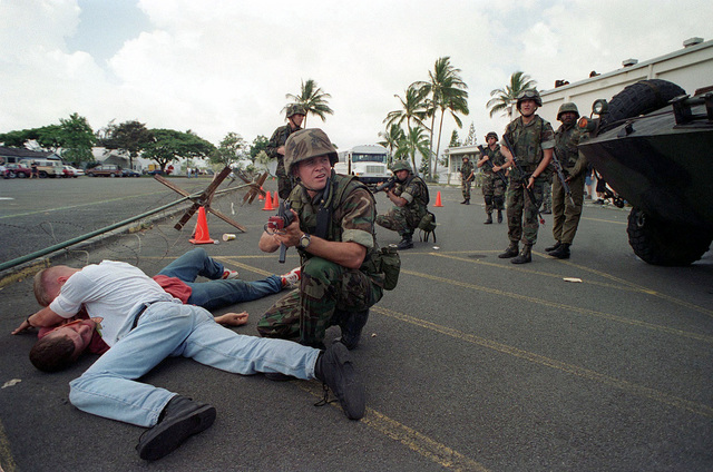 US Navy Hospital Corpsman Eric Carver armed with a 5.56mm M16A2 assault rifle, watches over two wounded civilians during a simulated Noncombatant Evacuation Operation (NEO) at Kaneohe Bay Marine Corps Station, Hi, during Operation RIMPAC 96. Marines from the 11th Marine Expeditionary Unit (MEU) Camp Pendleton, CA, conducted training in evacuation of civilians from hostile foreign environments