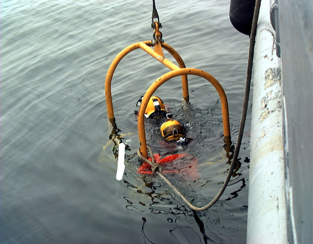 US Navy MASTER Diver Eric Frank and Diver James Mariano from Mobile Diving Salvage Unit 2 are inside a diving cage being lowered into the water at TWA Flight 800 crash site