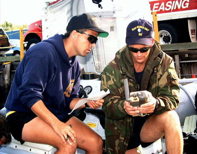 US Navy PETTY Officer 2ND (PO2) Class Travis OLeary (left) watches as PO2 Kai Fornes programs critical navigational information in a global positioning satellite transceiver. Both PO2 OLeary and Fornes are assigned to Explosive Ordnance Disposal (EOD) Mobile Unit Six, Charleston, SC supporting search and recovery efforts for TWA flight 800 crash site