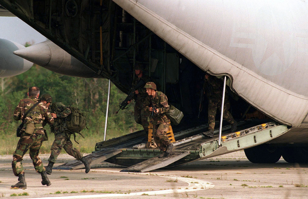 US Marine Corps soldiers from Company 4 step off a US Air Force C-130 Hercules aircraft at Davis Airfield, North Carolina, for Final Training Exercise (FTX) III, COOPERATIVE OSPREY 96. FTX III encompasses Airfield Security, Convoy Operations, and Humanitarian Assistance