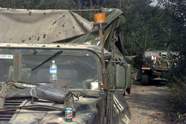 A 3/5 Cavalry US Army M1097 High-Mobility Multipurpose Wheeled Vehicle (HMMWV) Cargo/Troop Carrier (an open Mountain Dew can rests on the hood and bottled water rests on the dashboard) severely damaged by the explosive concussion of a Serbian TMA-1A Anti-tank Mine exploding after another US Army HMMWV struck and detonated the mine. This HMMWV was part of a convoy traveling in the Russian Brigade Area in Bosnia-Herzegovina