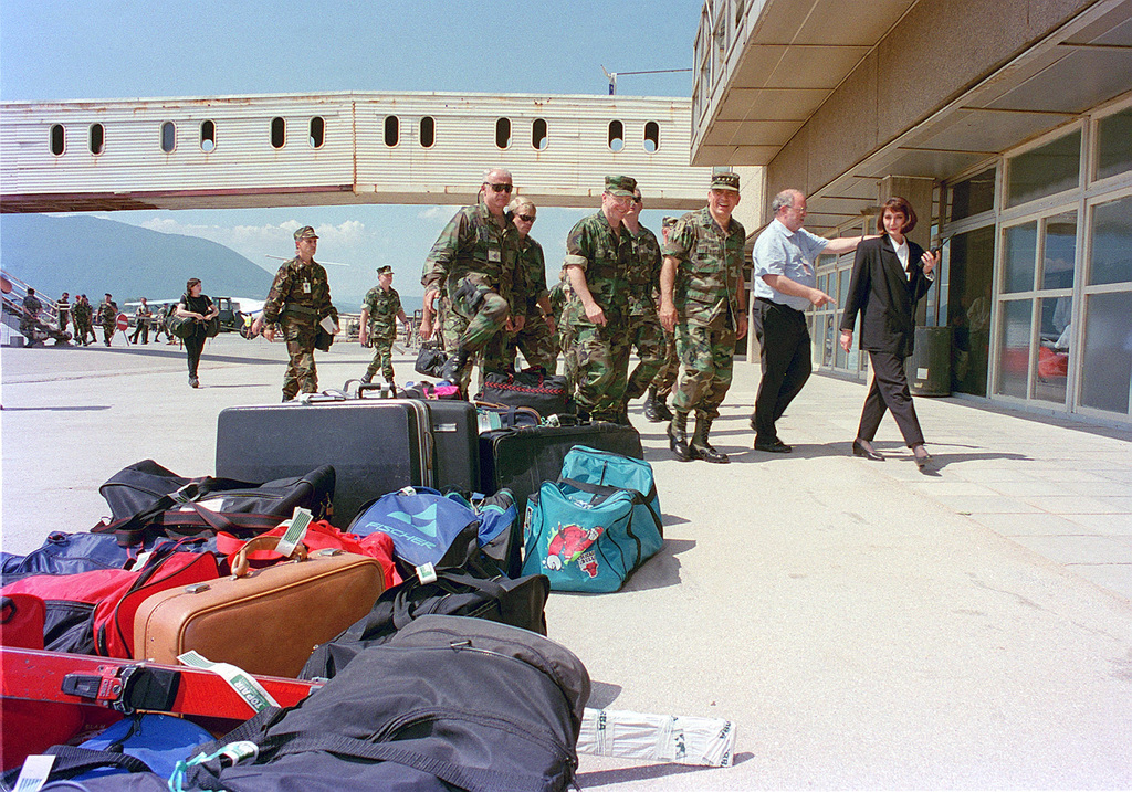 General George Joulwan, Supreme Allied Commander Europe (3rd from right), and Admiral T. Joseph Lopez, US Navy, Commander of the Peace Implementation Forces in support of Operation JOINT ENDEAVOR (the multi-national peace mission in Bosnia) (4th from right), visit the civilian departure terminal at the Sarajevo Airport in Bosnia Herzegovina. They walk by travelers' luggage lined up in a row for loading onto commercial aircraft. The terminal is currently refurbishing and repairing the building after it suffered damages during the recent civil war