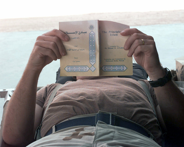 An airman reads about the culture and lifestyle of Saudi Arabia at Prince Sultan Air Base in Al Kharj, Saudi Arabia, in between off-loading aircraft in support of Operation SOUTHERN WATCH (monitoring the no-fly zone over Iraq)