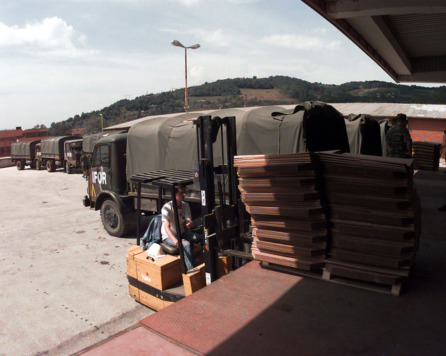 An OSCE (Organization for Security and Cooperation in Europe) staff members drives a forklift to pick up a pallet carrying polling kits off of a loading dock. These kits are loaded onto Greek Army, IFOR marked, Steyr 680 M (4x4) 4500 kg Trucks (seen behind the forklift) and then shipped throughout Bosnia-Herzegovina for the upcoming elections taking place during Operation Joint Endeavor. Operation Joint Endeavor is a peacekeeping effort by a multinational Implementation Force (IFOR), comprised of NATO and non-NATO military forces, deployed to Bosnia in support of the Dayton Peace Accords