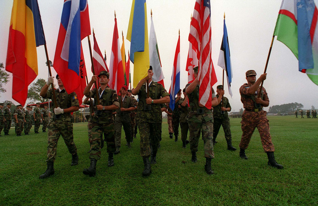 """Representatives from the Partner Nations carry their respective flags during the closing ceremony. Under the Partnership for Peace program, this exercise provided combined training in peacekeeping and humanitarian operations along NATO/IFOR standards, with emphasis on individual and collective skills. The 16 """"Partnership for Peace"""" nations contributing troops were Albania, Austria, Bulgaria, Estonia, Georgia, Hungary, Kazakhstan, Kyrgystan, Latvia, Lithuania, Moldova, Poland, Romania, Slovak Republic, Ukraine, and Uzbekistan. In addition, the following countries provided observers to the exercise: Azerbaijan, Belarus, Czech Republic, and Denmark"""