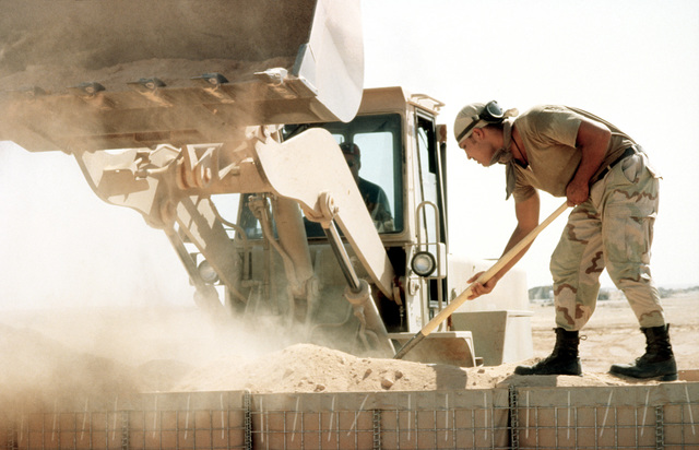 SENIOR AIRMAN David C. Quick, a member of the 823rd Red Horse Squadron from Hurlburt Field, Florida shovels the dirt that the bulldozer left out to make a revetment around one of the power producing facilities