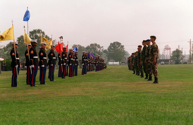 """US Marines from 6th Marine Regiment prepare to pass on their guidons to representatives from the Partner Nations during the closing ceremony. This United States Atlantic Command sponsored exercise conducted by Marine Forces Atlantic (MARFORLANT), under the Partnership for Peace program, provided combined training in peacekeeping and humanitarian operations along NATO/IFOR standards with emphasis on individual and collective skills. The 16 """"Partnership for Peace"""" nations contributing troops were Albania, Austria, Bulgaria, Estonia, Georgia, Hungary, Kazakhstan, Kyrgystan, Latvia, Lithuania, Moldova, Poland, Romania, Slovak Republic, Ukraine, and Uzbekistan. In addition, the following ..."""