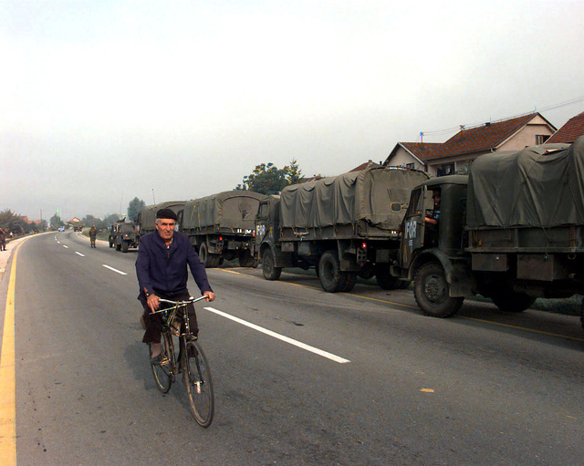 A Bosnian civilian bicyclist rides past a Greek Army, IFOR marked, military vehicle convoy parked on the roadside shoulder. This convoy includes four Steyr 680 M (4x4) 4500 kg Trucks, a M998 High-Mobility Multipurpose Wheeled Vehicle (HMMWV), and an unidentified vehicle and is carrying OSCE (Organization for Security and Cooperation in Europe) provided polling kits for the upcoming election to be held in Zenica, Bosnia-Herzegovina, during Operation Joint Endeavor. Operation Joint Endeavor is a peacekeeping effort by a multinational Implementation Force (IFOR), comprised of NATO and non-NATO military forces, deployed to Bosnia in support of the Dayton Peace Accords
