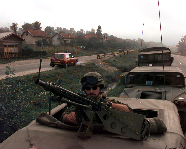 A Greek Army machine gunner, standing up through the gunner's hatch, inspects a 7.62mm MG3 Machine Gun attached to the top a military vehicle that is part of Greek Army convoy, parked on the roadside, protecting cargo trucks loaded with OSCE (Organization for Security and Cooperation in Europe) provided polling kits that are being shipped throughout Bosnia-Herzegovina for the upcoming elections taking place during Operation Joint Endeavor. Behind this first vehicle is a Greek Army M998 High-Mobility Multipurpose Wheeled Vehicle (HMMWV) and another unidentified vehicle. Operation Joint Endeavor is a peacekeeping effort by a multinational Implementation Force (IFOR), comprised of NATO and ...
