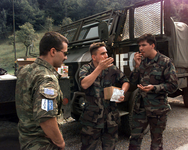 A Greek Army soldier observes SRA Kenneth J. Gabehart (USAF)and A1C Rick Haskins (USAF), Det. 1 Air Education Training Command/Training Support Squadron (AETC/TSS), tasting food from a Greek Army field lunch. These three individuals are standing in front of a two, parked Greek Army vehicles are part of a convoy carrying OSCE (Organization for Security and Cooperation in Europe) provided polling kits for the upcoming elections to be held in Doboj, Bosnia-Herzegovina, during Operation Joint Endeavor. Operation Joint Endeavor is a peacekeeping effort by a multinational Implementation Force (IFOR), comprised of NATO and non-NATO military forces, deployed to Bosnia in support of the Dayton ...