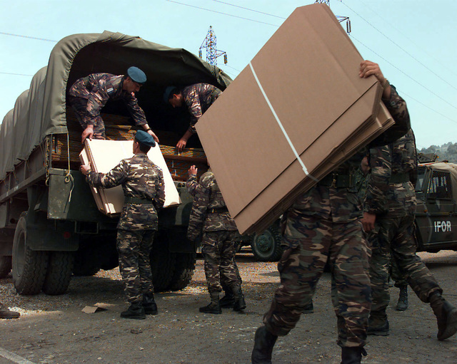 Turkish Army soldiers offload OSCE (Organization for Security and Cooperation in Europe) provided polling kits by hand from the back end of a Greek Army Steyr 680 M (4x4) 4500 kg Truck. These polling kits are for the upcoming elections to be held in Zenica, Bosnia-Herzegovina, during Operation Joint Endeavor. Operation Joint Endeavor is a peacekeeping effort by a multinational Implementation Force (IFOR), comprised of NATO and non-NATO military forces, deployed to Bosnia in support of the Dayton Peace Accords
