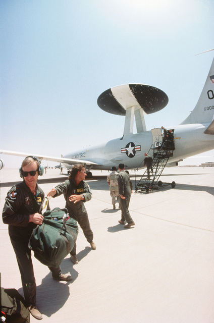 "Aircrew from the 557th Air Control Wing, Tinker Air Force Base, Oklahoma conduct a ""Bag Drag"" during their arrival in an E-3C Sentry Airborne Warning and Control System (AWACS) aircraft. This is the relocation of Operation Southern Watch from Dhahran after a terrorist bomb killed 19 Air Force personnel in June"