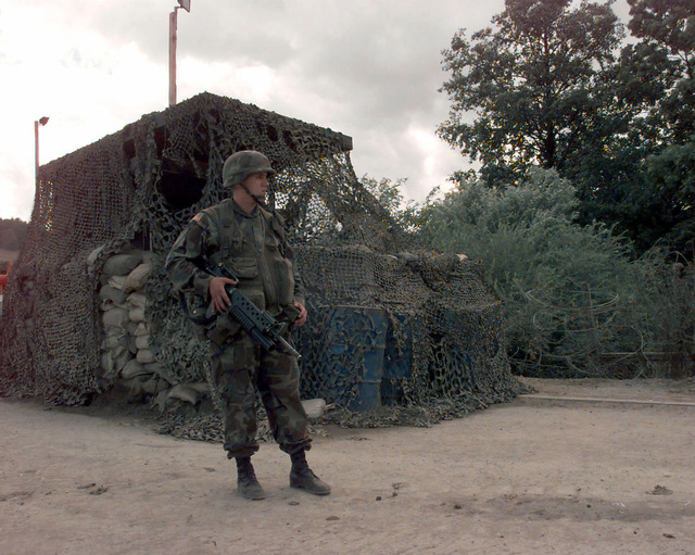 SPC Joshua Henry (USA), Indirect Fire Infantryman, HQ 268 Armored Battalion, 1ST Armored Division, stands guard, armed with a 5.56mm M16A2 Assault Rifle fitted with a 40mm M203 Grenade Launcher, in front of the camouflage-netting covered main entry control point bunker for Camp Linda Olovo, Bosnia-Herzegovina, during Operation Joint Endeavor. Operation Joint Endeavor is a peacekeeping effort by a multinational Implementation Force (IFOR), comprised of NATO and non-NATO military forces, deployed to Bosnia in support of the Dayton Peace Accords