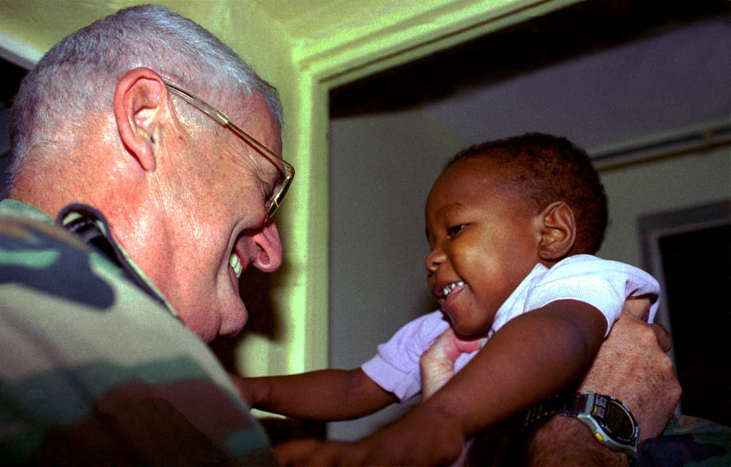 US Navy Captain John R. Downs, Commanding Officer, Humanitarian Relief Operation, holds a Haitian child at Vaudrveil Hospital in Croix-des-Bouquets outside of Port-au Prince, Haiti, during the humanitarian relief operation, Exercise FAIRWINDS '96