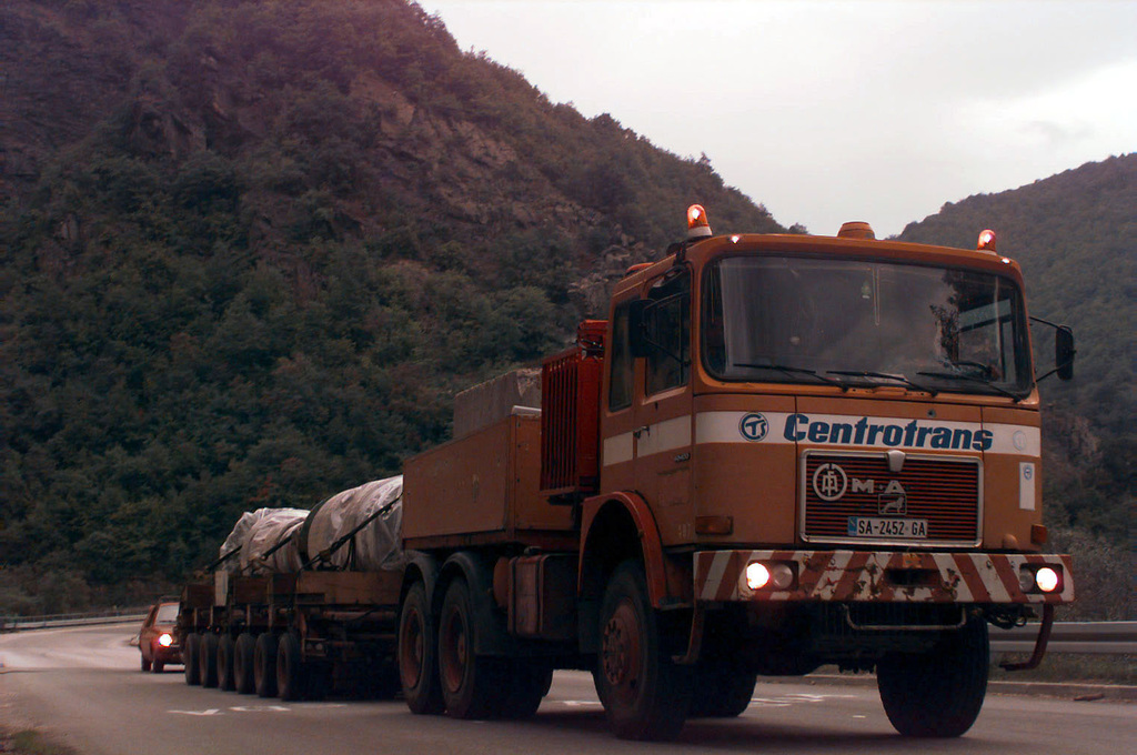 A commercial truck , followed by a Bosnian police car, tows a multi-wheeled trailer carrying a 70-ton turbine shaft. This turbine shaft was refurbished in Austria and is headed to a major hydroelectric plant in Salakovac, Bosnia-Herzegovina, which provided electrical power to the southern federation, but has not been in operation for four years