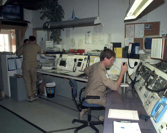 """Three Norwegian Army officers, one seated at a control panel and two in the background standing and talking together, work in the Norwegian Medical Company's (NorMedCoy) medical facility operations room at the """"Blue Factory,"""" located near Tuzla, Bosnia-Herzegovina. The Norwegians are in Bosnia as part of the Nordic-Polish (NORDPOL) Brigade in support of Operation Joint Endeavor, which is a peacekeeping effort by a multinational Implementation Force (IFOR), comprised of NATO and non-NATO military forces, deployed to Bosnia in support of the Dayton Peace Accords"""