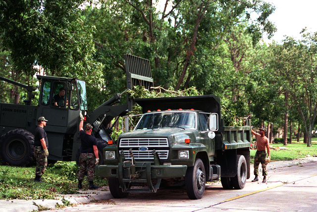 Personnel clear downed limbs and trees after Hurricane Fran ripped across the base the night of 5 Sep 96. Initial clean-up and recovery was performed primarily by on-base personnel, as members off-base had difficulty reaching the base due to hundreds of downed trees and power lines blocking all roads and highways in the area. (Duplicate image, see also DFSD0200685 or search 960906F9718G005)