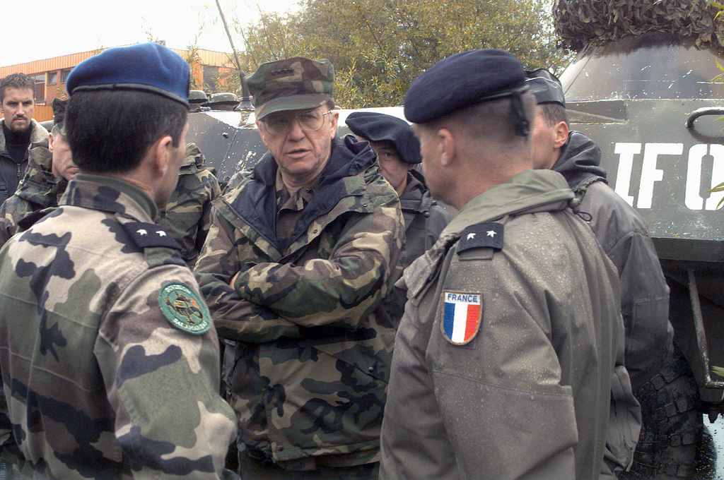 Admiral T. Joseph Lopez, US Navy, Allied Forces Southern Europe, United States Naval Forces Europe and Commander of the Implementation Forces (IFOR) in support of Operation JOINT ENDEAVOR (the multi-national peace mission in Bosnia), is briefed by French Army officers of the Multinational Division Southeast about a fatal gunshot incident that killed a Ukrainian IFOR tank crew member today. At the time of this writing, the incident was still under investigation. The Ukrainian soldier was killed at his post on the BTR eight wheeled armored tank, seen in the background. Military troops are here providing security of a voting material storage and election ballot processing warehouse....