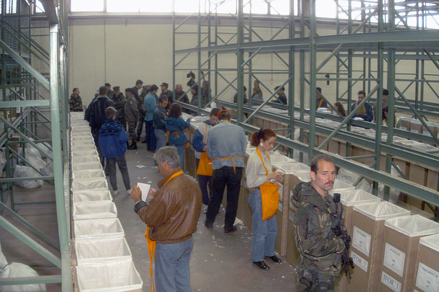In the main Organization for Security and Co-operation in Europe (OSCE) warehouse, Admiral T. Joseph Lopez (in background), US Navy, Allied Forces Southern Europe, United States Naval Forces Europe and Commander of the Implementation Forces (IFOR), tours through the facility while civilian election workers process absentee voting ballots. Each drop-box in the several rows represent one candidate for the national election. Regular elections will be held for six days. IFOR personnel are in Bosnia in support of Operation JOINT ENDEAVOR (the multi-national peace mission in Bosnia)