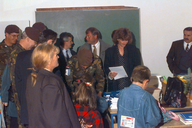 A Dutch Civil Affairs officer hands-out school books at the reopening of Radojka Lakic Primary School, Novo Sarajevo, Republika Srpska, during Operation JOINT ENDEAVOR (the multi-national peace mission in Bosnia)