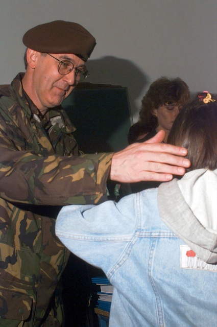 General Henk Noordhuizen, Dutch CHIEF of Civil Affairs, Allied Rapid Reaction Corps (ARRC), gives school books to a student at the reopening of Radojka Lakic Primary School in Novo Sarajevo, Republika Srpska, during Operation JOINT ENDEAVOR (the multi-national peace mission in Bosnia)