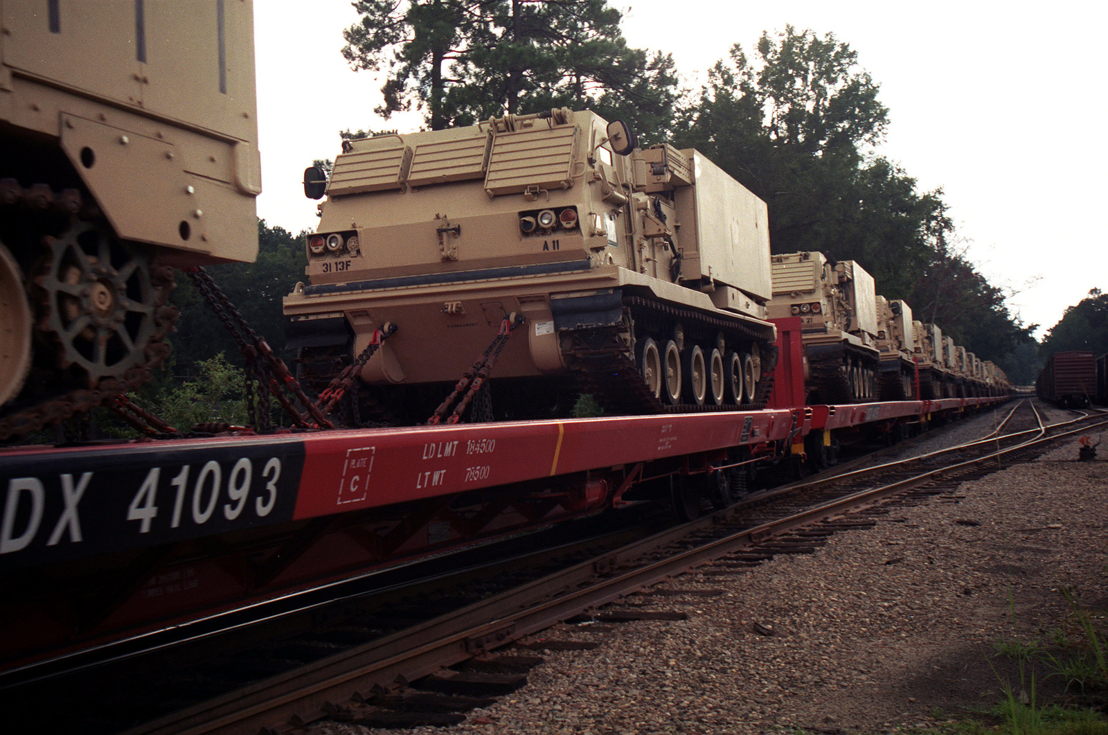 A number of multiple launch rocket systems (MLRS) are chained on railroad flatcars for transport between Ft. Stewart and Savannah, GA