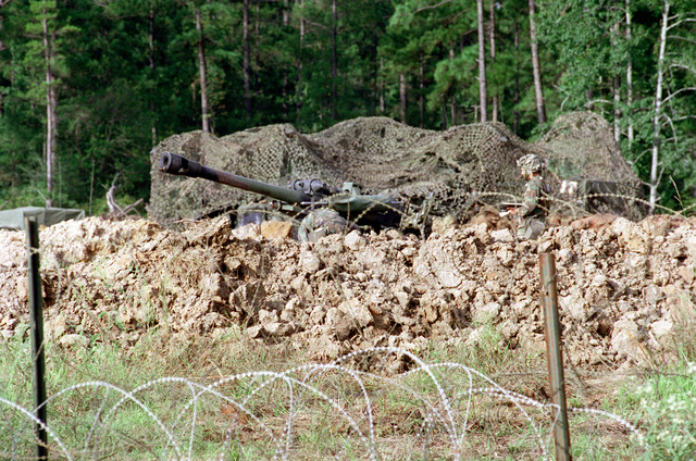 Against the backdrop of a forest, a 155mm Howitzer under camouflage provides artillery support to the 25th Infantry at the Joint Readiness Training Center. Obstacles of piles of dirt and concertina wire can be seen in the foreground