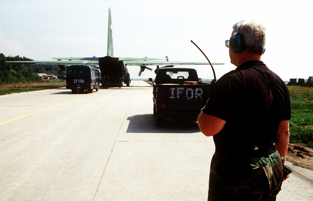TECH. SGT. Phillip Vanderwal from the 4100th Aerial Port Flight, Task Force Eagle, directs cargo being uploaded onto a C-130 aircraft. The aircraft is assigned with the 41st Airlift Squadron, Pope Air Force Base, N.C. and is deployed to Ramstein Air Base Germany