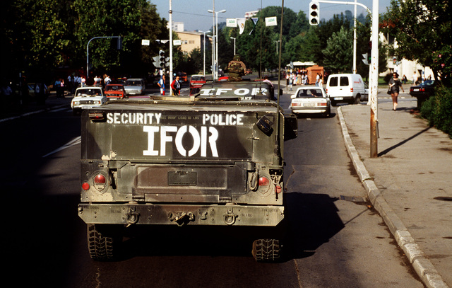 Two High-Mobility Multipurpose Wheeled Vehicles (HMMWV) in a convoy from the Security Police Squadron, 4100th Group Task Force Eagle, drive through the city of Tuzla looking for a local vendor to pick up some supplies. The HMMWV's are marked with Implementation Forces (IFOR)