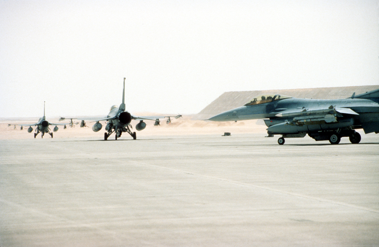 F-16 Fighting Falcons with the 69th Fighter Squadron, Moody Air Force Base, Georgia, roll out of the blocks as they taxi towards the runway. The Aircraft and personnel from the 69th Fighter Squadron are providing Fighter Aircraft support during the relocation of Operation Southern Watch and the 4404th Wing (Provisional ) from Dhahran after a terrorist bomb killed 19 Air Force personnel in June