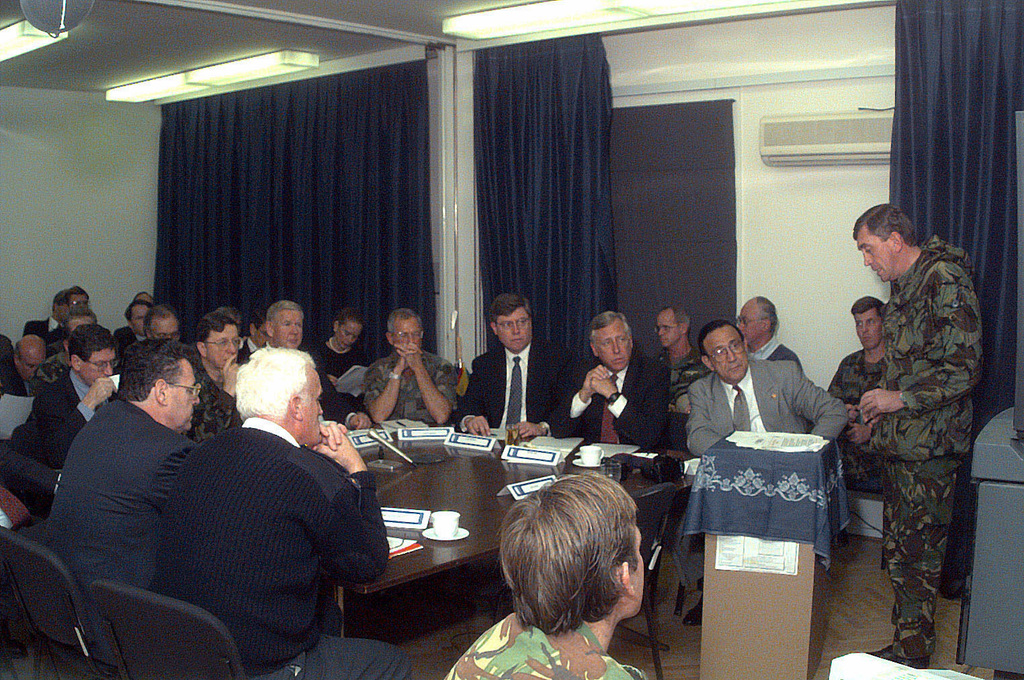 UK Army, Brigadier General Will Cook (right), presents an Implementation Forces (IFOR) election briefing to Representative John Murtha, Ambassador Richard Holbrooke, and a US Presidential delegation, in support of Operation JOINT ENDEAVOR. Seated at the table (clockwise from closest), Commissioner Peter Fitzgerald, International Police Task Force (IPTF); Representative Peter King; Ambassador John Kornblum; French Army Lieutenant General Jean Heinrich, Implementation Forces, Deputy Commander; Ambassador Richard Holbrooke; United States Navy Admiral T. Joseph Lopez, Allied Forces Southern Europe, United States Naval Forces Europe and Implementation Forces Commander; Representative John ...