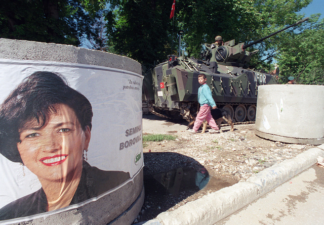 """A political poster was glued to several of the barriers in front of the Implementation Forces Headquarters. During the days leading up to the national elections of Bosnia and Herzegovina, people were free to attach posters such as this to any available vacant wall, pole, or in this case, tank barrier, thanks in part to Operation JOINT ENDEAVOR. Election day was what some officials termed """"boring"""" since voting was very peaceful"""