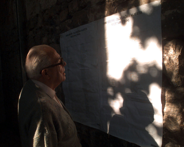 A voter looks over a list of polling stations in Mostar, Bosnia-Herzegovina. The list of stations was posted to show voters the different places to cast their ballots on the morning of the Bosnia-Herzegovina national elections
