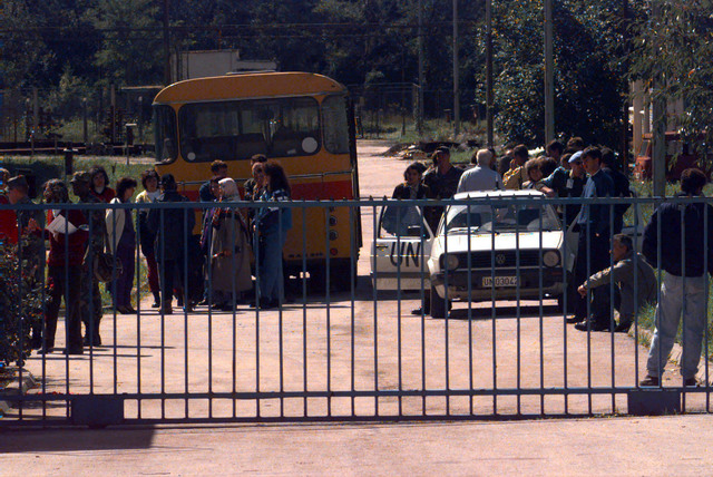 An extreme long shot of Muslim voters waiting in line at the segregated polling station near the town of Rogatica, Republic of Srpska. The Muslims arrived in buses accompanied by International Police Task Force on the morning of the Bosnia-Herzegovina national elections