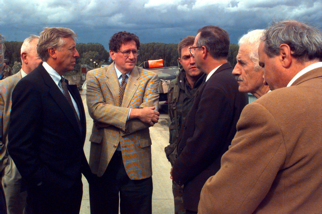 Congressman Steny Hoyer (left), D-Maryland, and Richard Holbrooke (center, left), United States mediator and architect of the Dayton Peace Agreement, talk with Miodrag Pajic (center, right with glasses), mayor of Brcko, Bosnia, about the elections, assisted by Department of Defense interpreter Dragan Minc (standing between Holbrooke and Pajic)