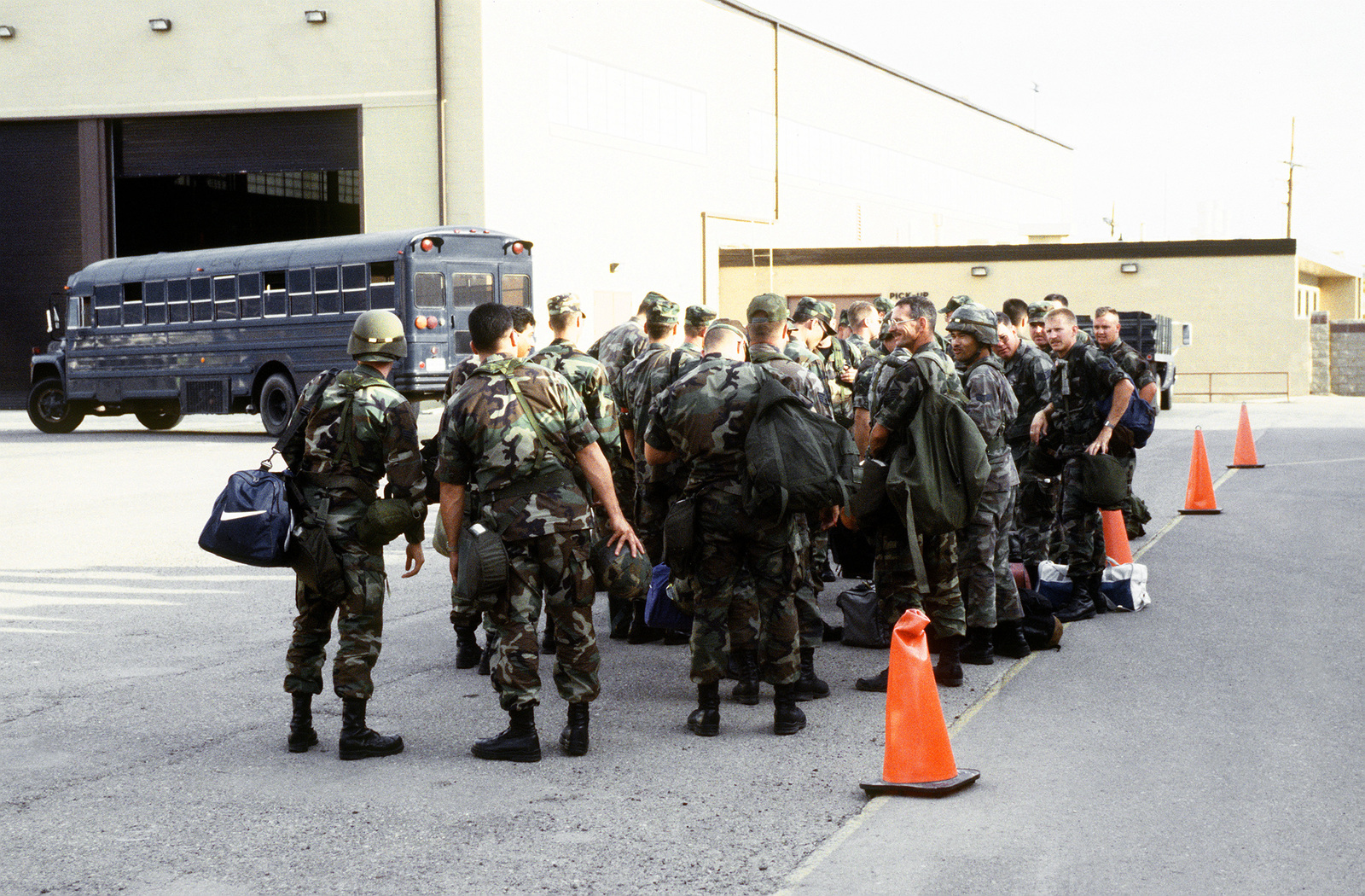 Members of the 9th Fighter Squadron await transportation for deployment to DESERT STRIKE. A blue Air Force bus is seen in the background