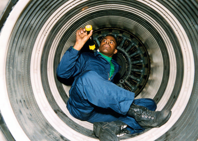 US Navy Aviation Machinist's Mate Second Class Jerome Porter inspects for foreign object damage in the interior of a F110 jet engine used on an F-14B Tomcat aircraft, during maintenance operations on board the US Navy's nuclear powered aircraft carrier USS ENTERPRISE (CVN 65). Enterprise, under the command of battle group commander US Navy Rear Admiral Martin J. Mayer (not shown), is transiting the Suez Canal and Red Sea enroute to the Persian Gulf in support of Operation SOUTHERN WATCH