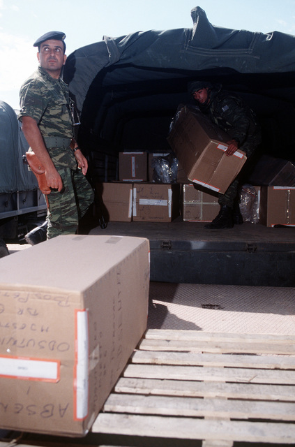 Implementation Forces (IFOR) troops unload boxes, containing election ballots at a warehouse. The ballots are to be separated and tabulated during the post-election process