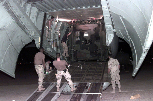 Members assigned to the 621st Air Mobility Control Squadron, McGuire Air Force Base, New Jersey, off-load a Mobile Air Reporting Center (M.A.R.C.), assigned to the 621st Air Mobility Operation Group, from a C-141B Starlifter aircraft, assigned to the 437th Airlift Wing, Charleston Air Force Base, South Carolina, at the Kuwait International Airport, Kuwait, in support of Operation DESERT FOCUS. The M.A.R.C. will be fully functional and able to communicate with incoming aircraft in less than 4 hours