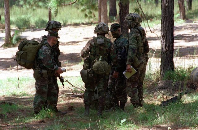Observers/Controllers, teaching, coaching and mentoring soldiers at the Joint Readiness Training Center. The soldiers are dress in camouflaged fatigues and camouflage paint. One soldier is carrying a backpack and three others are wearing camouflaged helmets