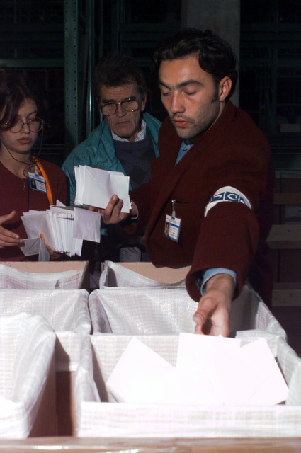 Vedad Tafro (foreground) and an interpreter from Sarajevo working for the Organization of Security and Cooperation in Europe, make sure ballots coincide with their respectable boxes. Implementation Force troops provided security, ensuring the Bosnia and Herzegovina election ballots made it to their proper destination during Operation JOINT ENDEAVOR